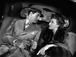 Trying to work his charm on Miss Bryant(Laraine Day).
